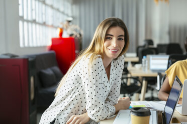 Portrait of smiling young woman at desk in office - EBSF02507