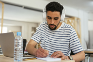 Young man wearing headphones taking notes at desk in office - EBSF02510