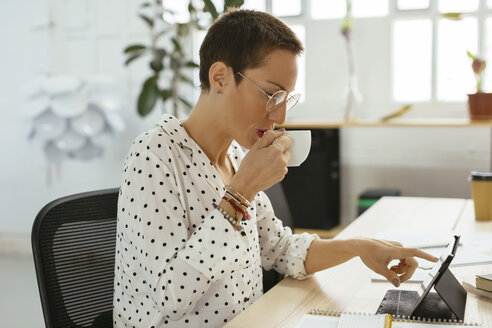 Woman drinking coffee and using tablet at desk in office - EBSF02516