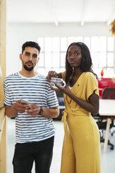 Portrait of two colleagues standing in office having a break - EBSF02546