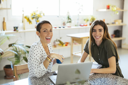 Portrait of two happy young women with laptop on table - EBSF02549