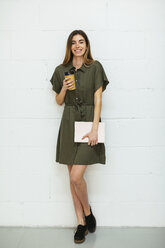 Portrait of smiling young woman with tablet and takeaway coffee standing at brick wall - EBSF02558