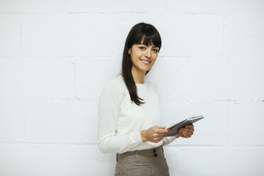 Portrait of smiling young woman with notebook at brick wall - EBSF02561