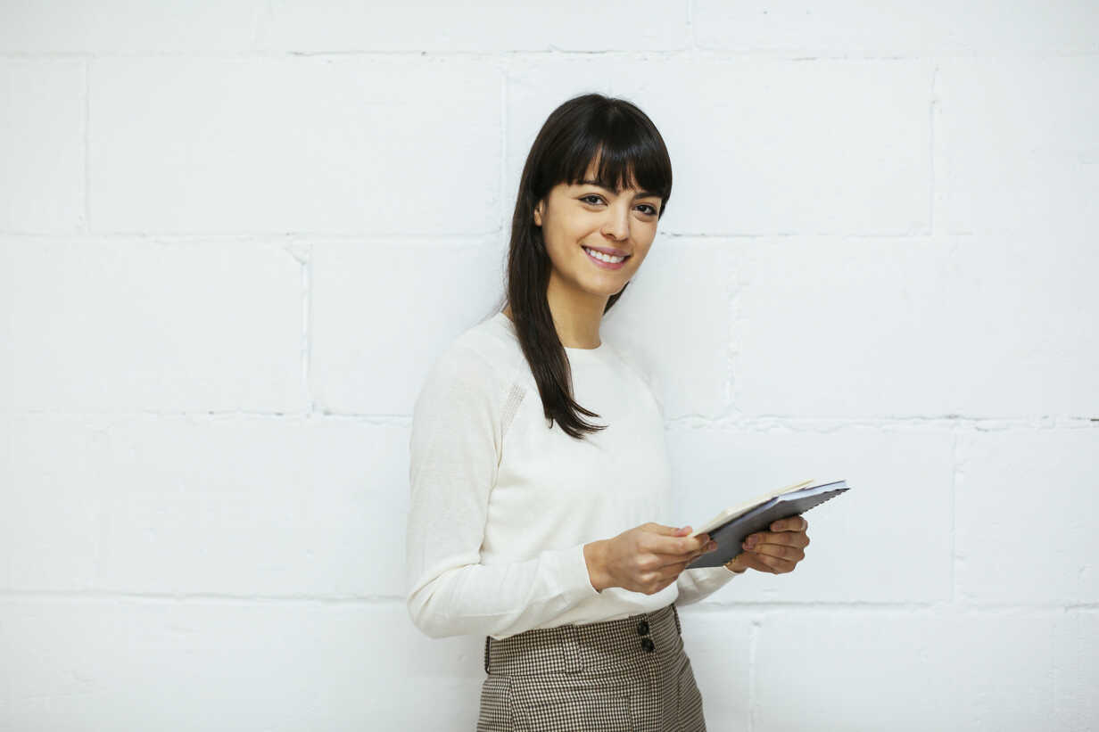 Portrait of smiling young woman with notebook at brick wall - EBSF02561 - Bonninstudio/Westend61