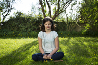 Girl sitting on meadow listening music with headphones - LVF06937