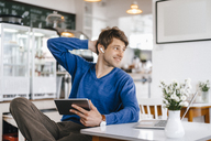 Smiling man in a cafe with earphone, laptop and tablet - KNSF03839