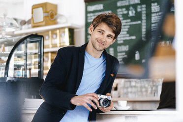 Smiling man in a cafe holding camera - KNSF03851