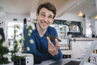 Smiling man in a cafe with cell phone and laptop - KNSF03875