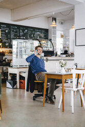 Smiling man in a cafe with laptop on cell phone - KNSF03878