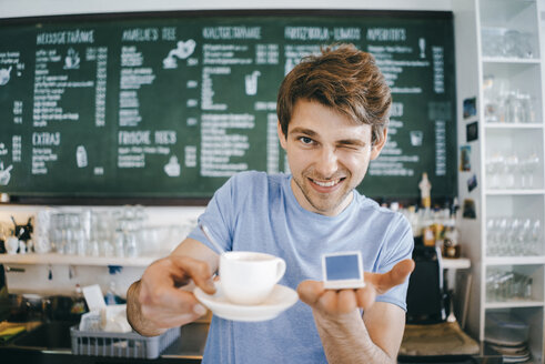 Smiling man in a cafe offering cup of coffee and holding miniature laptop model - KNSF03893