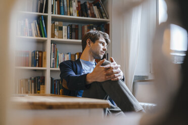 Man sitting at bookshelf looking sideways - KNSF03902