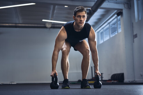 Man doing kettlebell exercise at gym - BSZF00310