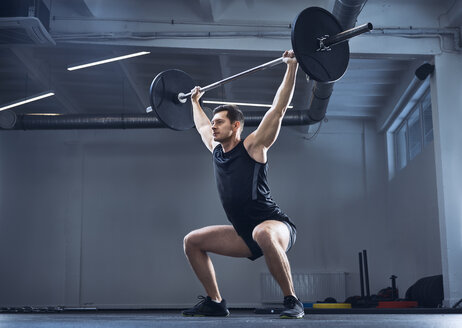 Man doing barbell exercise at gym during weight lifting workout - BSZF00313