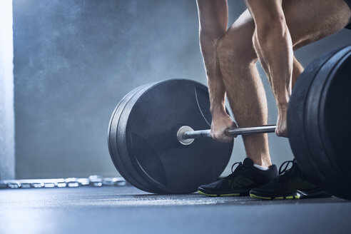 Close-up of man doing deadlift exercise at gym - BSZF00316