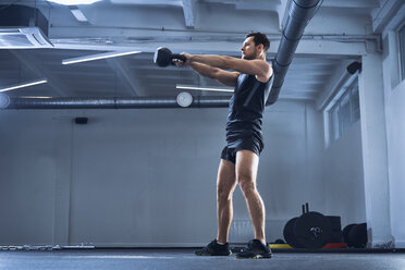 Athletic man doing kettlebell swing exercise at gym - BSZF00319