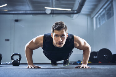 Athletic man doing pushups exercise at gym - BSZF00322