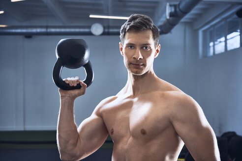 Athletic shirtless man posing with kettlebell at gym - BSZF00325