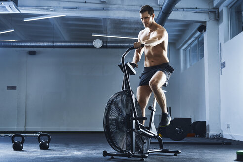 Athletic man doing HIIT workout on airbike at gym - BSZF00328