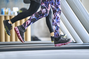 Close-up of people running on treadmill at gym - BSZF00331