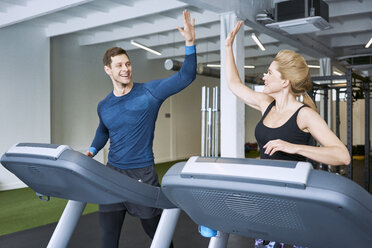 Happy man and woman doing high five during treadmill exercise at gym - BSZF00334