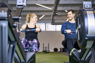 Man and woman at gym exercising together on rowing machines - BSZF00337