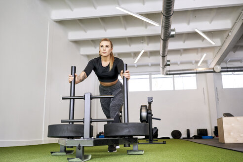 Woman pushing weight sled at gym - BSZF00340