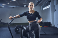 Athletic woman doing air bike workout at gym - BSZF00349
