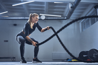 Athletic woman exercising with battle ropes at gym - BSZF00352