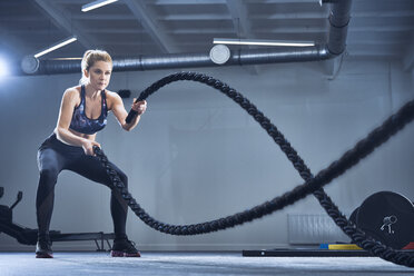 Athletic woman exercising with battle ropes at gym - BSZF00355