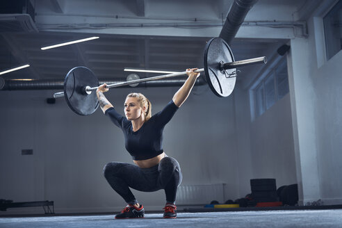 Woman doing overhead squat exercise at gym - BSZF00364