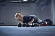 Woman practicing dumbbell push-up exercise at gym - BSZF00367