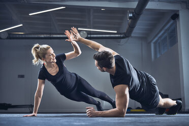 Man and woman doing high five during side plank exercise at gym - BSZF00373