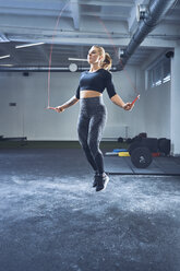 Athletic woman skipping with jumping rope in gym - BSZF00376