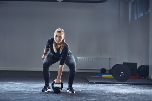 Woman exercising with kettlebell at gym - BSZF00379