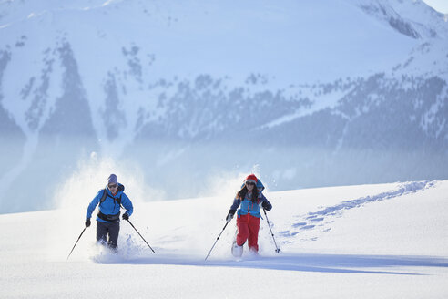 Austria, Tyrol, snowshoe hikers running through snow - CVF00418