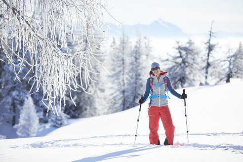 Austria, Tyrol, smiling snowshoe hiker standing in snow - CVF00421