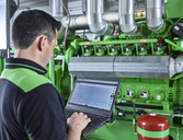 Combined heat and power plant, worker using laptop in front of gas engine - CVF00439