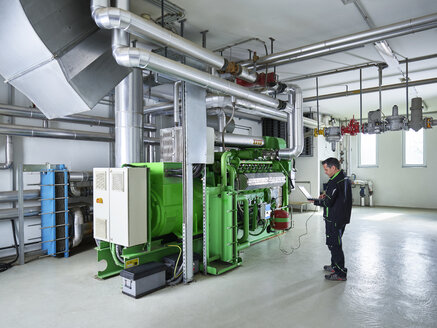Combined heat and power plant, worker using laptop in front of gas engine - CVF00442