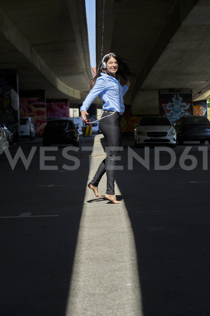 Cheerful young woman with headphones and cell phone dancing barefoot at underpass - BEF00032 - Benjamin Egerland/Westend61