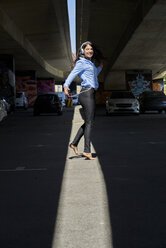 Cheerful young woman with headphones and cell phone dancing barefoot at underpass - BEF00032