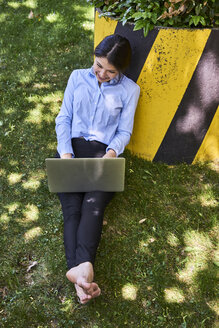Young businesswoman sitting barefoot on a meadow using laptop - BEF00035