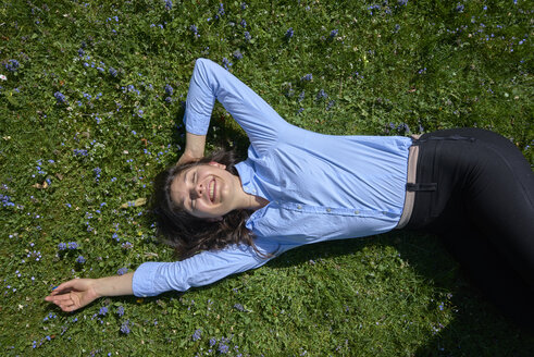 Portrait of happy young woman relaxing on a meadow - BEF00041