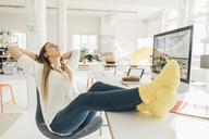 Young freelancer relaxing with feet up at desk in a loft - GUSF00746