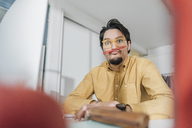 Portrait of freelancer pulling funny faces at desk - GUSF00752