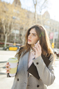 Spain, Barcelona, young businesswoman with coffee to go on the phone - VABF01563