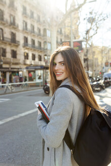 Spain, Barcelona, portrait of smiling young woman with backpack standing at street - VABF01566