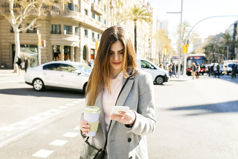 Spain, Barcelona, young woman with coffee to go standing at roadside looking at cell phone - VABF01581