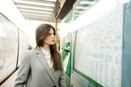Spain, Barcelona, portrait of young businesswoman looking at map at station - VABF01584