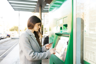 Spain, Barcelona, woman buying ticket from automated machine at  station - VABF01587
