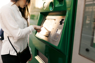 Spain, Barcelona, woman buying ticket from automated machine at  station - VABF01590
